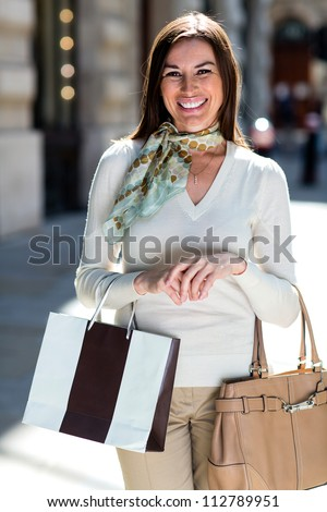 Happy female shopper holding shopping bags and smiling - stock photo