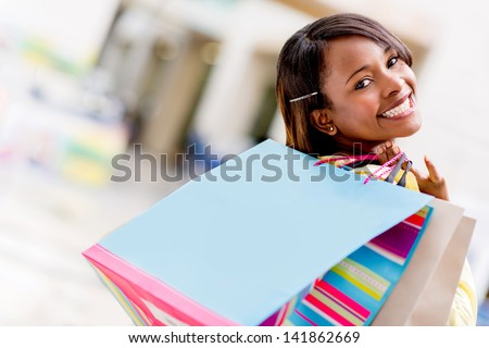 Happy female shopper with shopping bags and smiling - stock photo