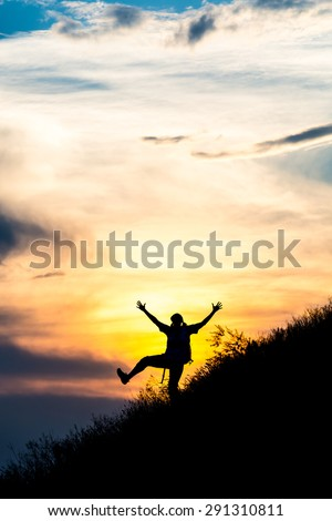 Happy female silhouette making funny dance. Woman making dancing moves on steep grassy hill with gorgeous sunset sky and cloudscape on background - stock photo