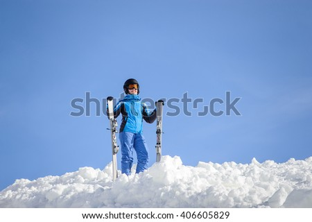Happy female skier standing on top of the mountain against blue sky on a sunny day, wearing blue ski suit helmet and goggles on sunny day. Girl is holding her skis. Winter sports concept.