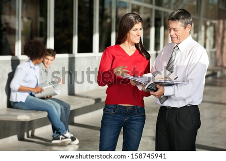 Happy female student and teacher discussing over book on college campus