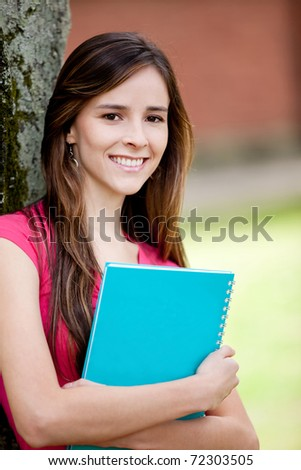 Happy female student carrying notebooks outdoors