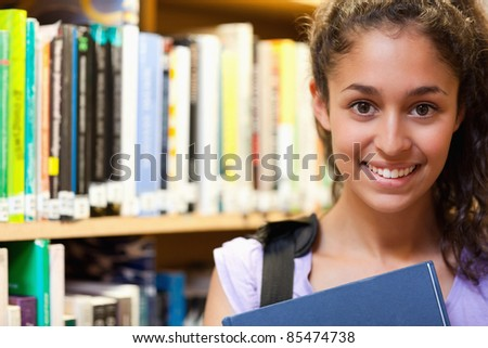 Happy female student holding a book in a library - stock photo
