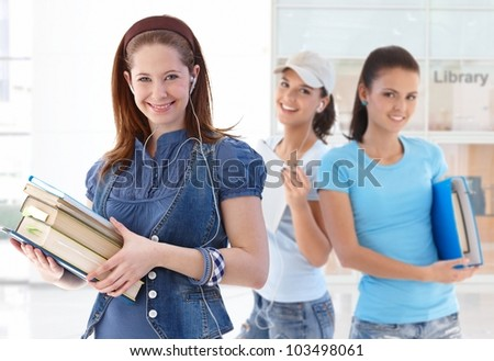Happy female student holding book in library lobby looking at camera friends in background. - stock photo