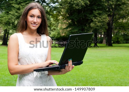 Happy female student holding notebooks and smiling outdoors.