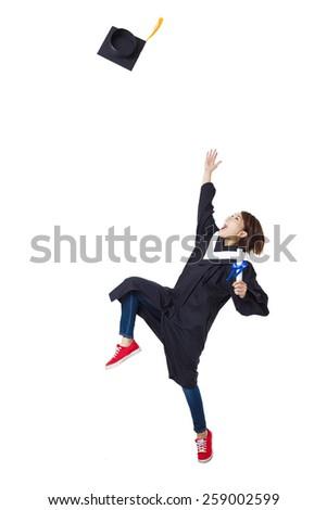 Happy female student in graduate robe dancing - stock photo