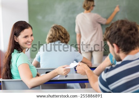 Happy female student passing note to friend in the classroom - stock photo