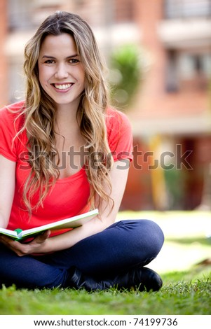 Happy female student sitting outdoors with notebooks