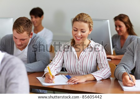 Happy female student taking notes in university class - stock photo