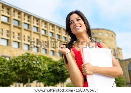 Happy female student walking in european college campus. Higher education successful woman. Universidad Laboral, Gijon, Asturias, Spain. Girl on university. - stock photo