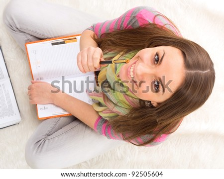 Happy female student with a laptop and notebooks