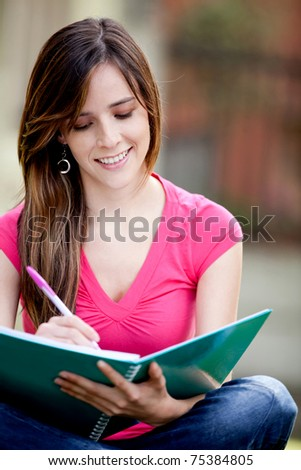 Happy female student with a notebook outdoors