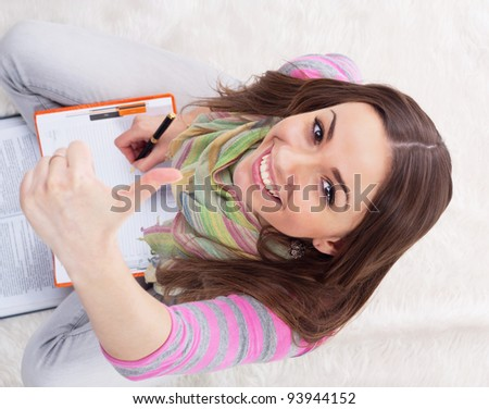 Happy female student with notebooks showing thumbs up sign