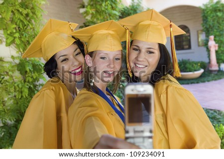 Happy female students self photographing in graduation gown - stock photo