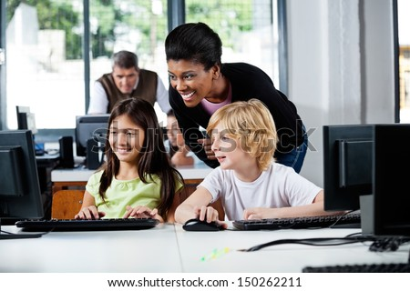 Happy female teacher assisting schoolchildren in using computer at school - stock photo