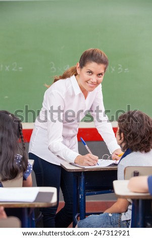 Happy female teacher checking students work at primary school.