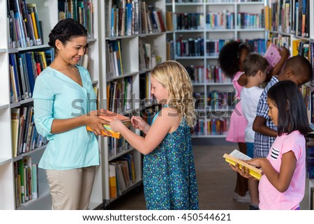 Happy female teacher giving books to girl in library