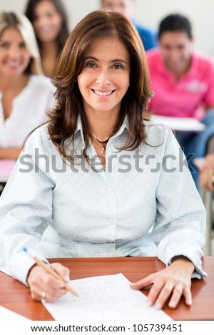 Happy female teacher in a classroom at the university - stock photo