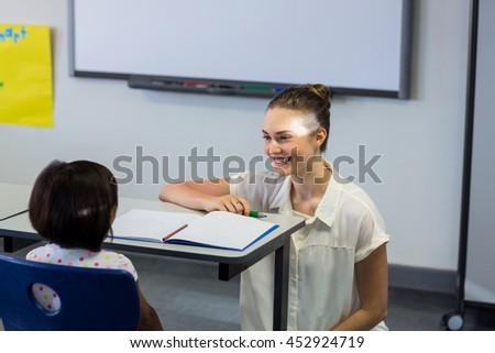 Happy female teacher kneeling by schoolgirl in classroom - stock photo