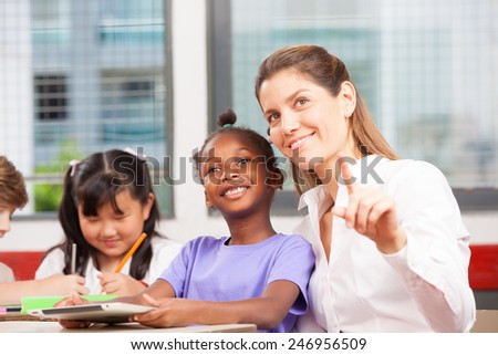 Happy female teacher showing something to multi ethnic primary classroom. - stock photo