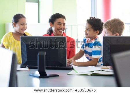 Happy female teacher with children in computer class - stock photo