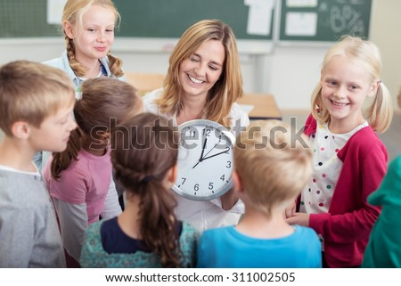 Happy Female Teacher with Wall Clock, Teaching her Students How to Read Time Inside the Classroom. - stock photo