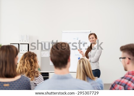 Happy Female Team Leader Discussing Some Business Matters Using a Poster Paper to the Group Inside the Office. - stock photo