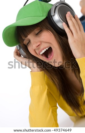 Happy female teenager enjoy music on white background, with headphones and baseball cap - stock photo