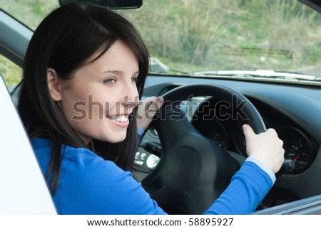 Happy female teenager sitting in her new car looking out of the window - stock photo