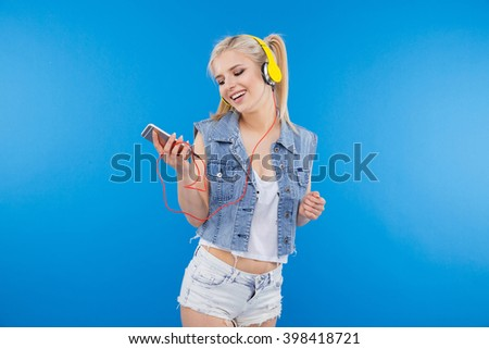 Happy female teenager using smartphone with headset over blue bakground