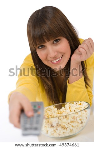 Happy female teenager watching television holding remote control, eating popcorn - stock photo