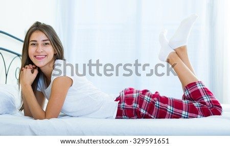 Happy female teenager with long hair relaxing in bed  - stock photo