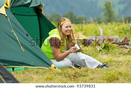 Happy female tourist drinking tea in front camp tent - stock photo