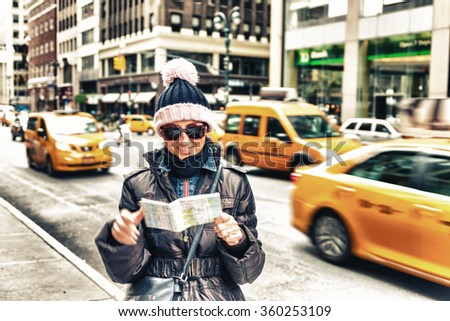 Happy female tourist in New York looking at city map. - stock photo