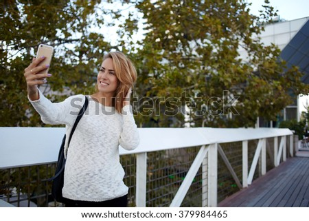 Happy female tourist photographing herself via cell telephone camera while standing on a bridge near house, cheerful European woman shoots video on mobile phone while strolling in spring day outdoors - stock photo