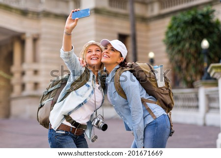 happy female tourists taking a self portrait with smart phone - stock photo
