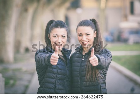 Happy female twins showing thumbs up at park. They are smiling and looking at camera. They wear similar clothes and they both have ponytail hair. - stock photo