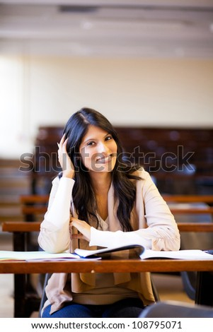 happy female university student in lecture hall - stock photo