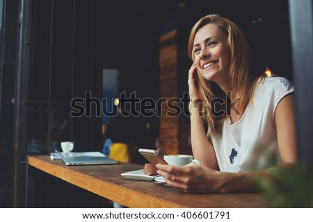 Happy female using smart phone while relaxing in cafe after walking during her summer weekend, charming smiling hipster girl received good news on cell telephone while she sitting in cozy coffee shop - stock photo