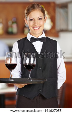 Happy female waiter with two red wine glasses in a restaurant - stock photo