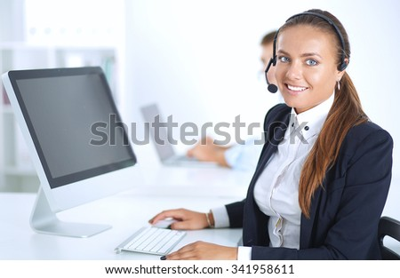 Happy female wearing headset and sitting on the desk