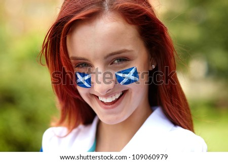 Happy female with Scottish flags on her cheeks, outdoor - stock photo
