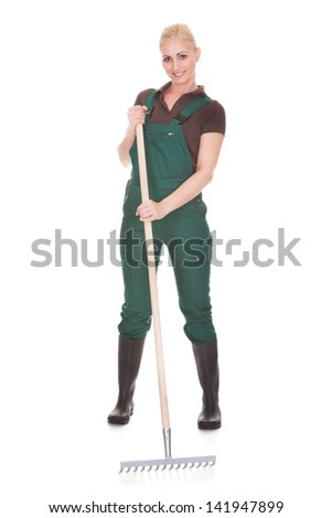 Happy Female Worker Holding Pitchfork Over White Background - stock photo