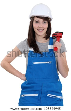 Happy female worker holding wrench - stock photo