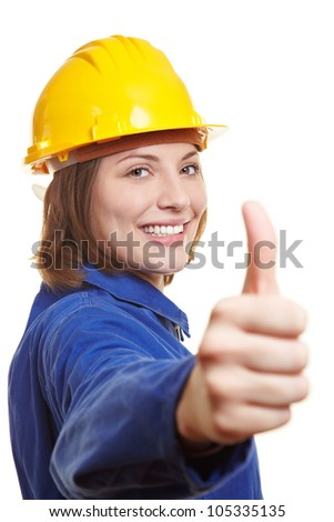 Happy female worker in blue overall and hardhat holding thumbs up - stock photo