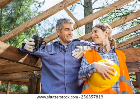 Happy female worker looking at colleague holding coffee mug at construction site - stock photo