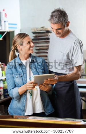 Happy female worker looking at male colleague while holding digital tablet in paper factory