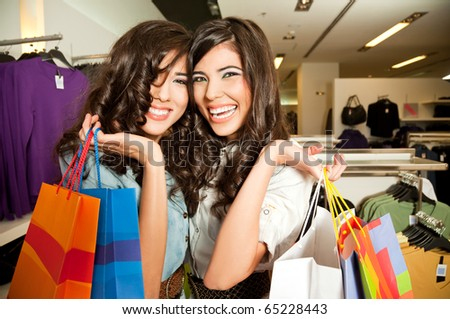 Happy females posing with shopping bags in fashion boutique - stock photo