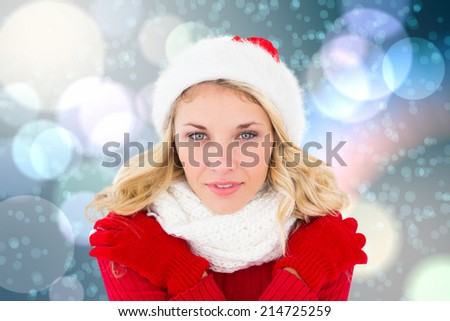 Happy festive blonde against light glowing dots on blue