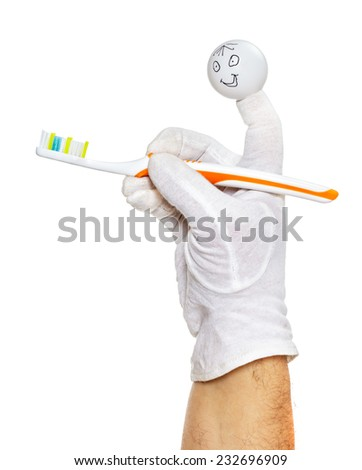 Happy finger puppet holding tooth brush isolated over white - stock photo